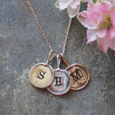 stamped initial necklace with gold, rose gold and silver charms