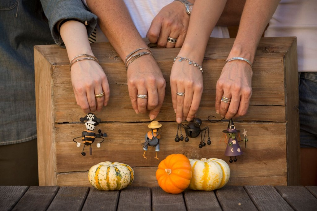 hands with jewelry holding toys and pumpkins
